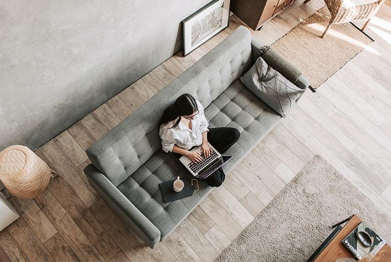 femme avec ordinateur portable sur sofa avec plancher de bois franc